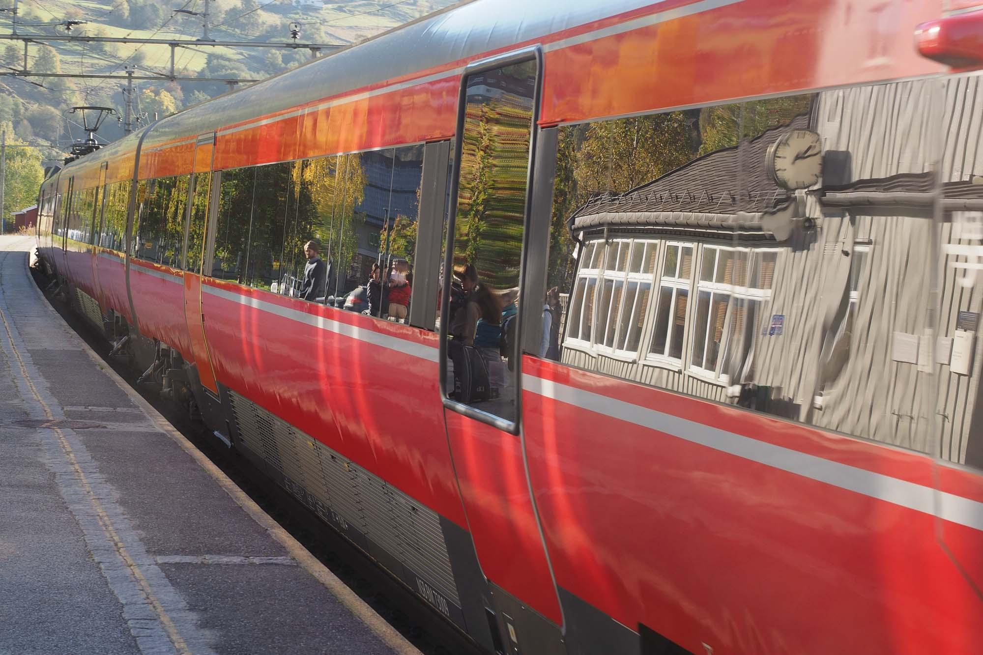 """Tittel: Det røde toget. Tema for Landsbygalleriet denne vinteren er """"Rødt"""". Jeg valgte å fotografere et rødt togsett som kjører inn på Ringebu stasjon. I togvinduene speiles stasjonsbygningen og forventningsfulle mennesker som gleder seg til å ta i mot venner og familie. Det første toget til Ringebu kom i november 1896, for akkurat 120 år siden. Det gikk mellom Hamar og Otta. Jernbanen over Dovrefjellet ble ikke bygget før på 1920-tallet. Helt fram til 1960-tallet ble togene drevet av kullsvarte damplokomotiv. Da hadde de gule eller rustrøde dieseldrevne togsettene tatt over fullt ut. Nå drives togene elektrisk og motefargen er rødt. Stasjonen fikk navnet Ringebu. Men bygdefolket holdt fast på """"Vålbrua"""", eller bare """"Brua"""" som navn på stasjonsbyen. Toget skapte grunnlaget for handel, virksomheter og vekst. Herfra styrte Bertrand Narvesen sitt kiosk kompani. Om stasjonsbyen, Gudbrandsdalens sentrum, skrev Lillehammer- humoristen """"Immen"""" Imerslund ei vise med mange vers: """"For når ni-toget det tute / inn på Ringebu stasjon, hele bygda dit må kute. / Det er dagens sensasjon. Vekk med gamp og øks og sagblad / vi må ned og kjøp oss Dagbla' Ja, for både folk og fe / er det blitt et samlingssted."""" I """"Hemgrenda 2015"""" har Erling Sæther skrevet utførlig om jernbanen i Ringebu."""