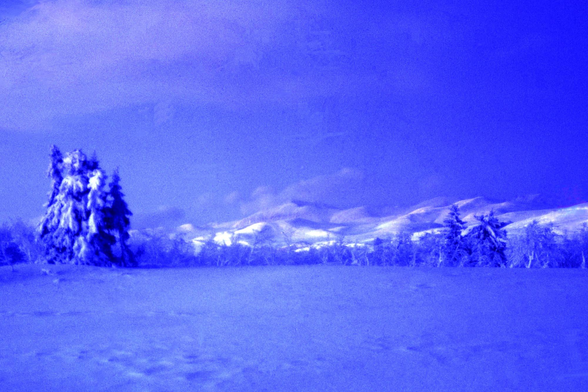 Bildet er fra Venabygdsfjellet, der Langbakken begynner. En runder den slake svingen, og panoramautsikten mot Rondane åpner seg. Fjellene har alltid vært der, mens lys og årstider gjør at de oppleves forskjellig. Sommer, høst, vinter og vår, aldri helt like, men fjellene er stadig de samme. Den som har opplevd soloppgang - spesielt om vinteren - på dette stedet glemmer det aldri. Å se de første røde og varme solstrålene bre seg - først på toppene dernest over hele fjellrekka - det er rett og slett magisk. Dette bildet ble tatt rundt midnatt. På veg over fjellet dukket månen fram bak skylaget, og mange blå grader skapte et lys jeg ikke har opplevd før eller siden. Heldigvis hadde jeg med både kamera og stativ, og med eksponeringstid på et par minutter ble øyeblikket foreviget. Av alle bilder jeg har tatt er kanskje dette jeg er mest glad i, opplevelsen av å oppleve et slikt lys og få foreviget det er stor. Jeg glemmer det aldri - heldigvis.