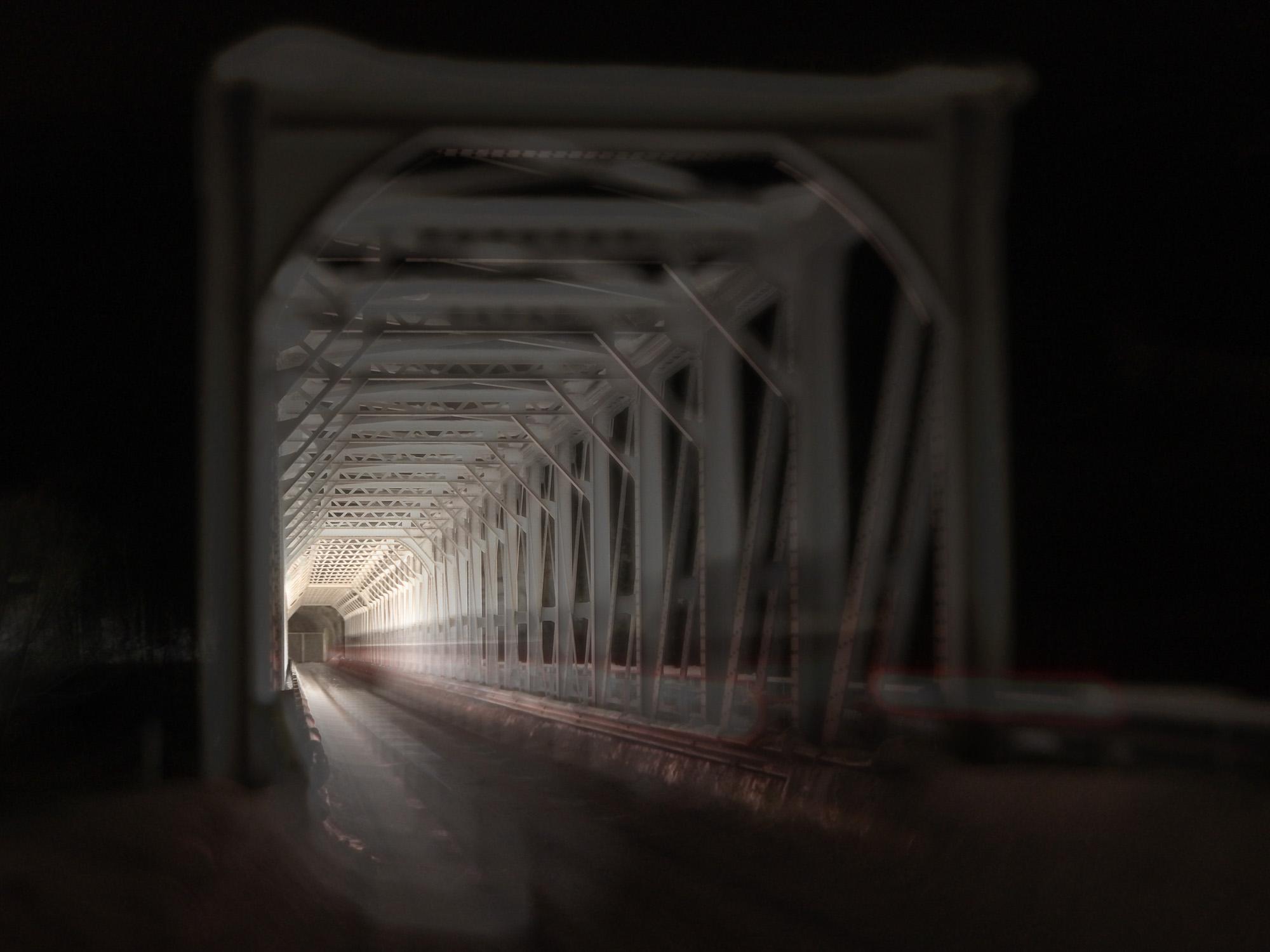 Sen februarkveld 2018 ved laugen i Ringebu og det er lys i enden av tunellen eller Randklev bro da som her. Temaet for utstillingen denne gang var bevegelse og at bildet skulle være tatt med mobiltelefon. Bildet mitt er tatt med iPhone 7 plus, iso 20, 8 sekunder @F2.8. Min kone Elin kjørte bilen over broen og med fem sekunders selvutløser på kameraet som jeg satte i gang. Så traff vi da som nogenlunde med bildet i det bilen kjørte ut på broen. Telefonen kom fra en varm bil og ut i kulden og satt på ett stativ, der skoddet den seg til litt og det ga det litt drømmende eller skumle utrykket i bildet.