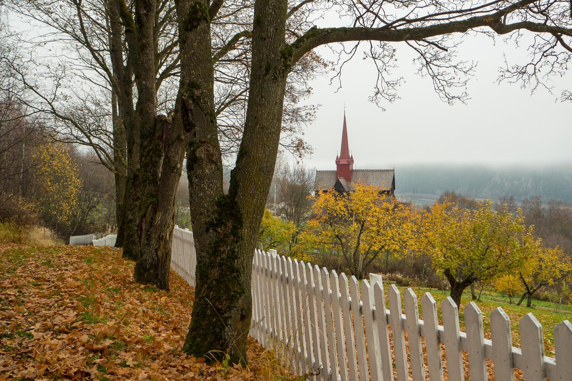 SNART VINTER Bildet er av Ringebu stavkirke. Det ble tatt i begynnelsen av november 2015. Dette bildet er ett av mange av vår lirke, men dette er tatt fra en litt annen vinkel enn normalt. Det er tatt fra stien mellom prestegården og ned mot kirka med store trær og et stakittgjerde. Ringebu stavkirke er bygget ca 1220. Den er en av 28 gjenværende stavkirker i Norge, og en av de største. Ringebu stavkirke er av Borgundtypen. Kirka har en utskåret inngangsportal i dragestil, som det er lagd en skulptur av ved enden av gangbrua i Ringebu sentrum.